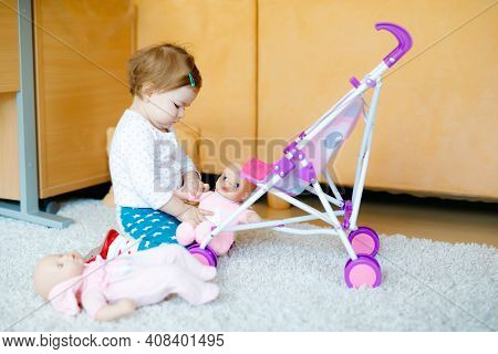 Cute Adorable Baby Girl Crawl And Play With Doll Carriage. Beautiful Toddler Child With Pushing Stro