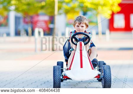 Active Little Kid Boy Driving Pedal Race Car In Summer Garden, Outdoors. Child Racing With Fast Spee