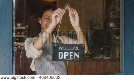 Young Asia Manager Girl Changing A Sign From Closed To Open Sign On Door Cafe Looking Outside Waitin