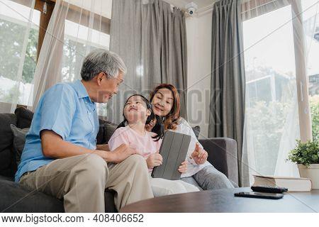 Asian Grandparents And Granddaughter Using Tablet At Home. Senior Chinese, Grandpa And Grandma Happy