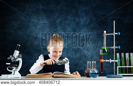 Little Girl Sitting At Desk With Magnifier And Open Book. Research And Education In School. Happy Sc
