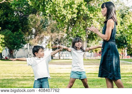 Two Happy Cute Kids And Their Mom Playing Active Games Outdoors, Doing Exercises On Grass In Park. F