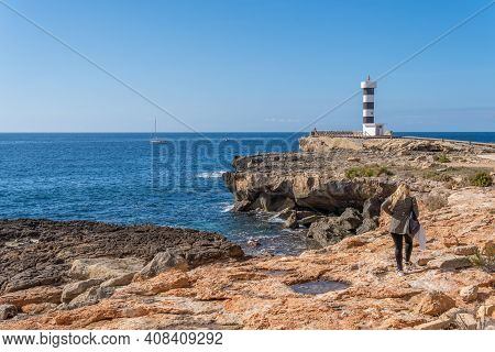 Colonia De Sant Jordi Lighthouse On A Sunny And Winding Day With A Person With His Back Turned And U