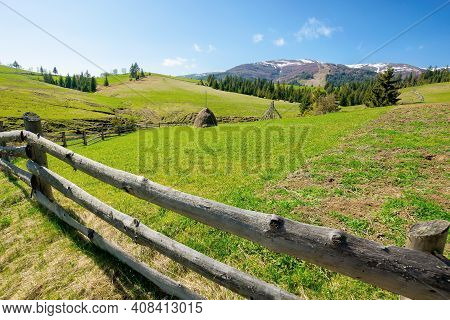 Mountainous Rural Landscape In Spring. Haystack On A Grassy Field Behind The Wooden Fence On Rolling