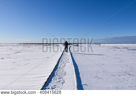 Man Walking On A Trail In An Open Winter Landscape In A Swedish Nature Reserve On The Island Oland