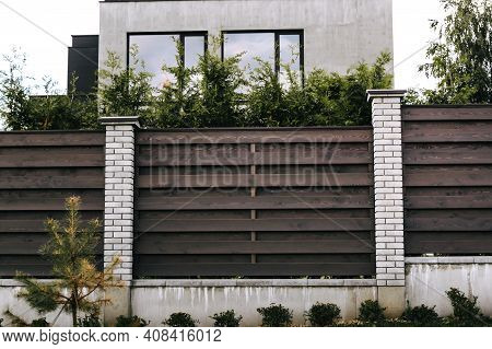 Horizontal Sections Of Brown Wooden Boards Fence And White Brick Pillars. Live Plantings. Green Thuj