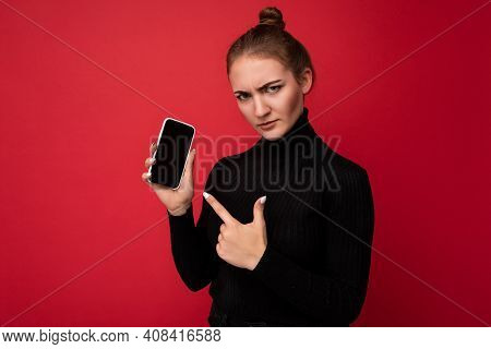 Angry Sad Attractive Positive Young Brunette Woman Wearing Black Sweater Standing Isolated Over Red