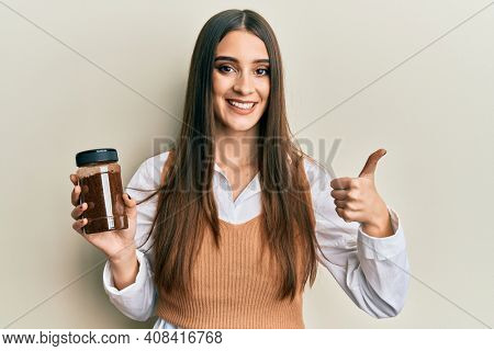 Beautiful brunette young woman holding soluble coffee smiling happy and positive, thumb up doing excellent and approval sign