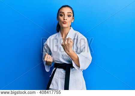 Beautiful brunette young woman wearing karate fighter uniform with black belt doing attack pose looking at the camera blowing a kiss being lovely and sexy. love expression.