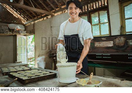 Asian Man Using An Electric Hand Mixer Up Some Cookie Batter Beside Baking Sheet Cake