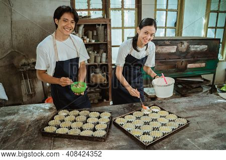 Smiling Asian Boy And Girl Wearing An Apron Looking At The Camera As They Pour The Cake Batter Onto