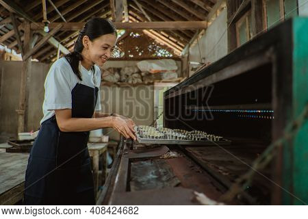 Smiling Woman Wearing An Apron Tossing The Pan Of Cake Batter Into The Oven