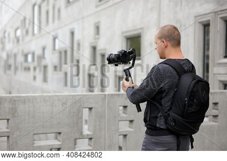 Filmmaking, Hobby And Creativity Concept - Back View Of Professional Videographer Shooting Video Usi