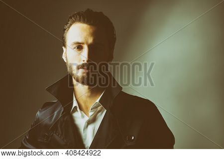 Portrait of a brutal handsome man with dark hair and a beard posing in black coat and white shirt. Men's beauty. Copy space.