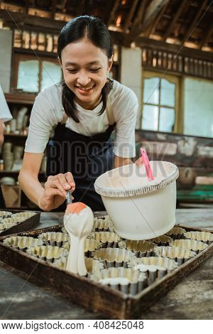 Close Up Of An Asian Girl Wearing An Apron Holding A Ladle Of Dough To Pour Into The Small Cake Mold