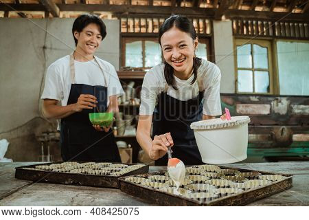 Smiling Asian Woman Wearing Apron Looking At The Camera As She Pours The Cake Batter On The Cake Tin