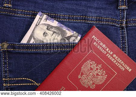 A Stack Of American Hundred Dollar Bills In The Back Pocket Of Blue Jeans And An International Passp
