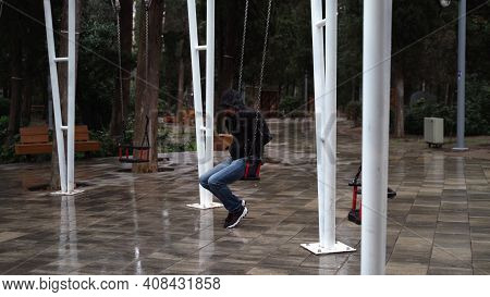 Lonely Man In The Park Swinging On A Swing. A Sad Man In Depression Is Lonely Swinging On A Swing In