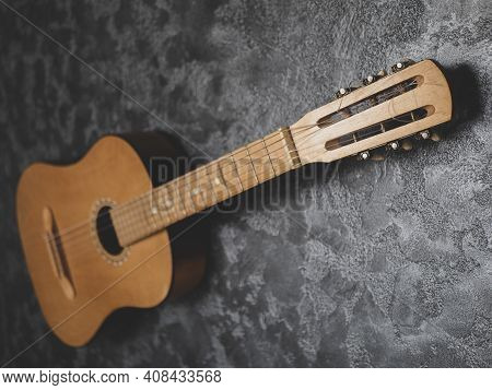 Acoustic Guitar On The Grey Textured Background. Old Vintage Headstock Close Up, Selective Focus