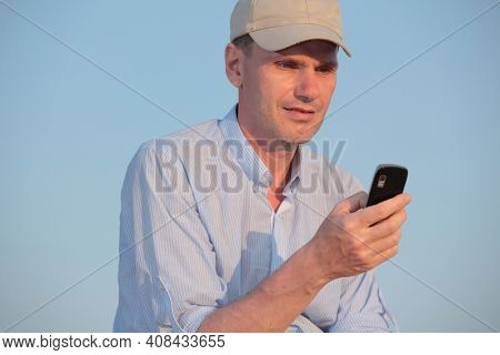 Man reading sms on obsolete mobile phone