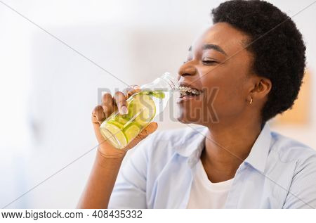 Refreshment. Happy African Woman Drinking Infused Water Posing With Bottle Indoors. Healthy Drink, N