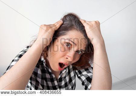 Horrified Young Woman Looking In Mirror Staring Open Mouthed At The First Grey Hair On Her Scalp, A