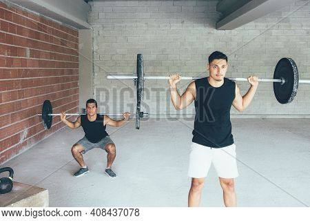 Pair Of Young Fit Men Doing Squats Exercises With Barbell At The Gym. The Back Man Out Of Focus. Wor