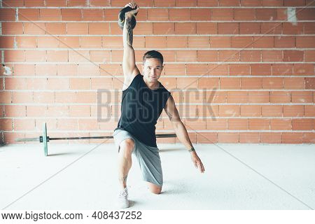 Fitness Young Man Doing A Weight Training By Lifting Kettle Bell. Young Athlete Doing Kettle Bell Li