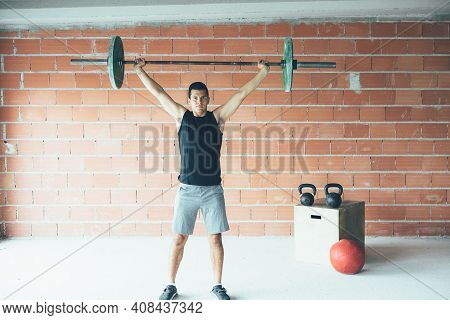 Front View Of A Man Doing Overhead Dead Lift With A Barbell In A Gym. Athletic Man Training His Arms