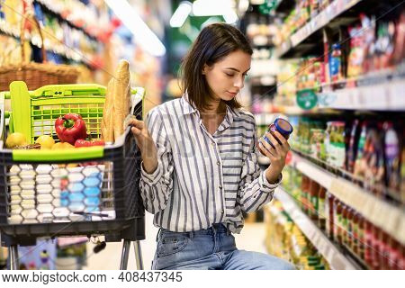 Consumption And Consumerism. Portrait Of Young Woman With Shopping Cart In Market Buying Groceries F