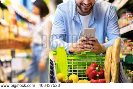 Closeup Of Unrecognizable Man Using Mobile Coupon App For Groceries Shopping Buying Food In Supermar