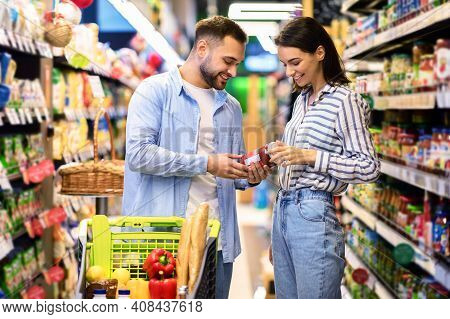 Customers In Super Market Concept. Young Family Couple Doing Grocery Shopping In Supermarket Choosin