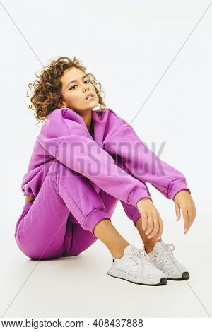 Sportswear fashion. Young girl model posing in a bright sportswear and sneakers on a white background. Studio shot.