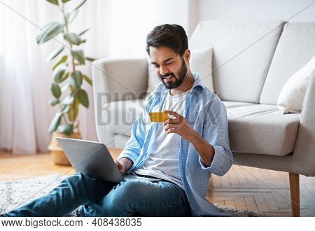 Millennial Arab Guy Making Online Payments With Laptop And Credit Card At Home, Sitting On Floor In