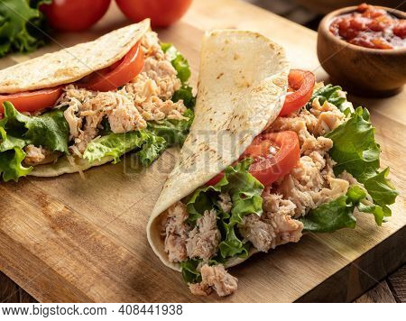 Closeup Of Two Chicken Tacos With Lettuce And Tomato On A Wooden Cutting Board