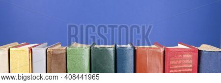 Simple Composition Of Hardback Books, Raw Books On A Blue Background. Stacking Of Books Without Insc