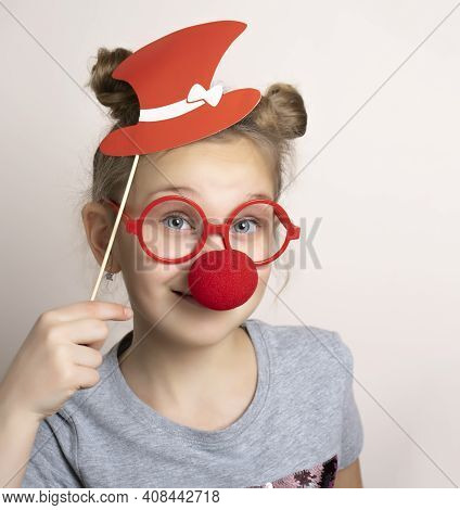 Happy Smiling Little Girl In Cute Carnival Mask With Clown Nose, Paper Hat And Eyeglasses. Festive C