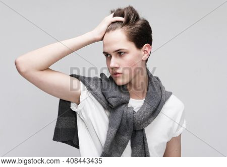 young handsome teenage hipster guy posing against grey background isolated, lifestyle people concept close up