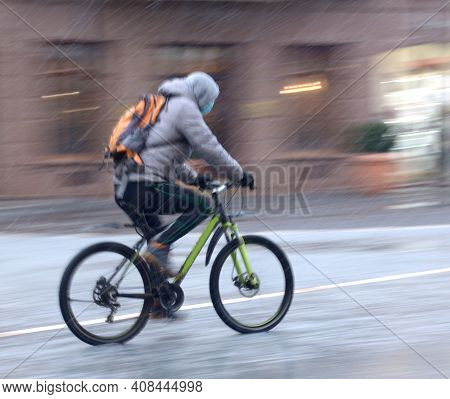 Cyclist On The City Roadway On A Rainy Day In Motion Blur. Defocused Image