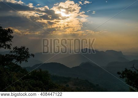 Sun-rays Piercing Through Dark Clouds At Dusk, Engulfs The Valley Below In Its Radiance