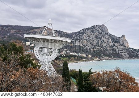 Large Astronomical Radio Telescope On The Seashore Against The Backdrop Of Mountains