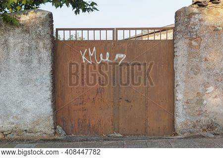 Rusty Door Of An Old Factory In Southern Spain, With A Nice Blue Sky
