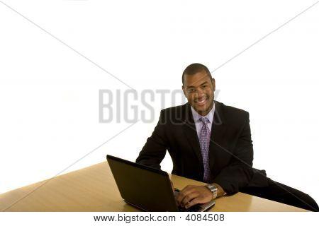 Black Man Working On Laptop Smiling At Camera