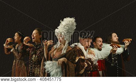 Fast Food Tastes Good. Medieval People As A Royalty Persons In Vintage Clothing On Dark Background.