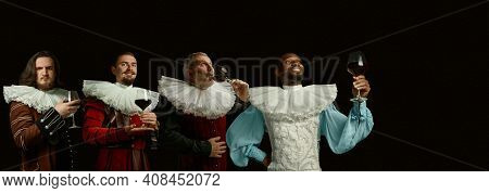 Enjoy Delicious Red Wine. Medieval Men As A Royalty Persons In Vintage Clothing On Dark Background.