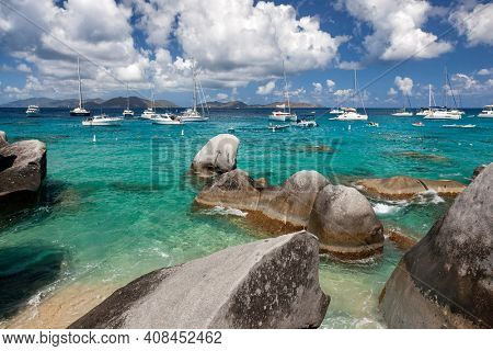 Boulders dot the shoreline of the Baths with boats moored in the distance at the Baths on Virgin Gorda in the British Virgin Islands.