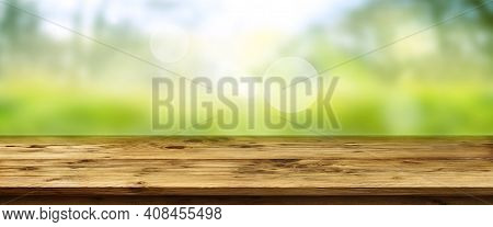 Blurred Green Landscape With Shining Bokeh And Wooden Table. Horizontal Spring Background With Space