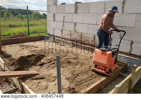 The Worker Controls The Vibrating Plate At The Construction Site, Heavy Manual Construction Equipmen