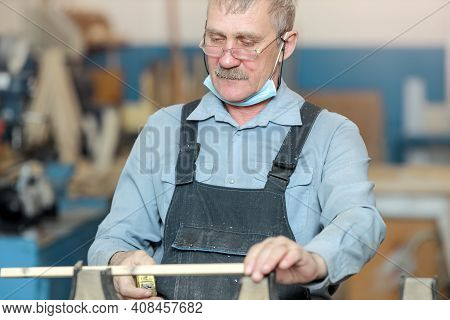 An Old Carpenter With A Mustache And Glasses Is Concentrating On His Work. An Elderly White Man Meas