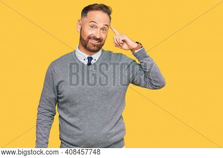 Handsome middle age man wearing business clothes smiling pointing to head with one finger, great idea or thought, good memory